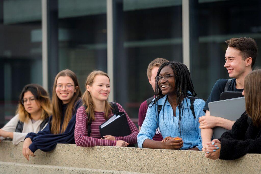 Des élèves universitaires sont regroupés à sourire ensemble